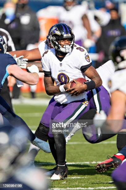 Quarterback Lamar Jackson of the Baltimore Ravens tries to avoid the rush during their AFC Wild Card Playoff game against the Tennessee Titans at...