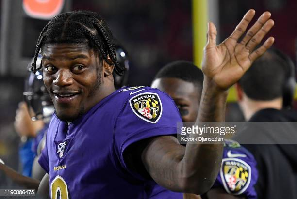 Quarterback Lamar Jackson of the Baltimore Ravens waves from the sidelines during the game against the Los Angeles Rams at Los Angeles Memorial...