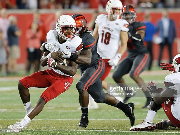 Quarterback Lamar Jackson of the Louisville Cardinals is sacked by linebacker Steven Taylor of the Houston Cougars in the second quarter at TDECU...
