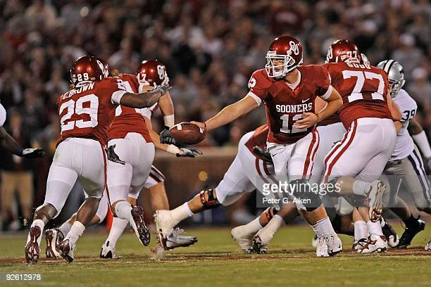 31 Quarterback Landry Jones of the Oklahoma Sooners gets ready to hand the ball off to running back Chris Brown in the second half against the Kansas...