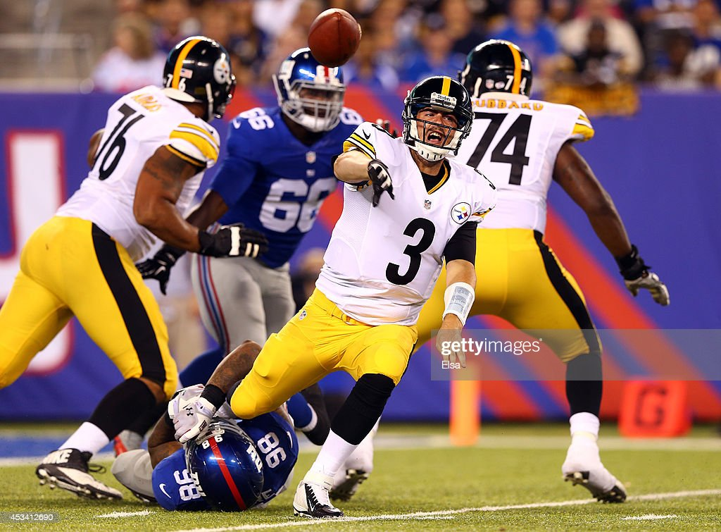 Quarterback Landry Jones #3 of the Pittsburgh Steelers makes a throw as he is tackled by defensive end Damontre Moore #98 of the New York Giants during a preseason game at MetLife Stadium on August 9, 2014 in East Rutherford, New Jersey.