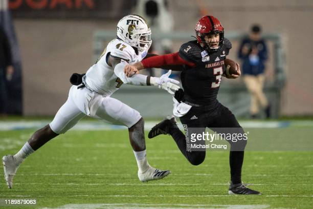 Quarterback Layne Hatcher of the Arkansas State Red Wolves looks to run the ball by linebacker Chris Whittaker of the FIU Golden Panthers in the...