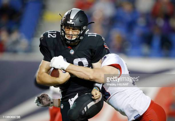 Quarterback Luis Perez  #12 of the Birmingham Iron is tackled by Davis Tull of the Memphis Express during the second quarter of their Alliance of...