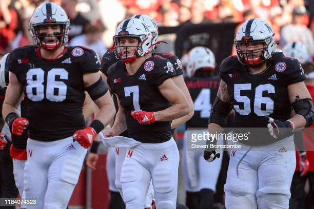 Quarterback Luke McCaffrey of the Nebraska Cornhuskers leads tight end Jack Stoll and offensive lineman Boe Wilson on the field during the game...