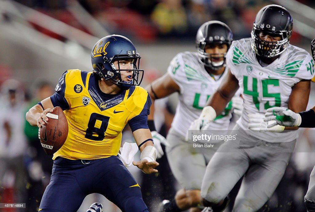 Quarterback Luke Rubenzer #8 of the California Bears scrambles under pressure from defensive lineman T.J. Daniel #45 of the Oregon Ducks in the second quarter on October 24, 2014 at Levi's Stadium in Santa Clara, California.