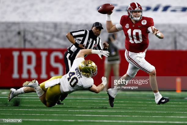 Quarterback Mac Jones of the Alabama Crimson Tide delivers a pass over linebacker Drew White of the Notre Dame Fighting Irish during the first...