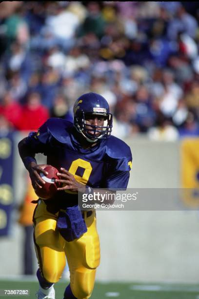 Quarterback Major Harris of the West Virginia University Mountaineers scrambles during a college football game at Mountaineer Field circa 1990 in...