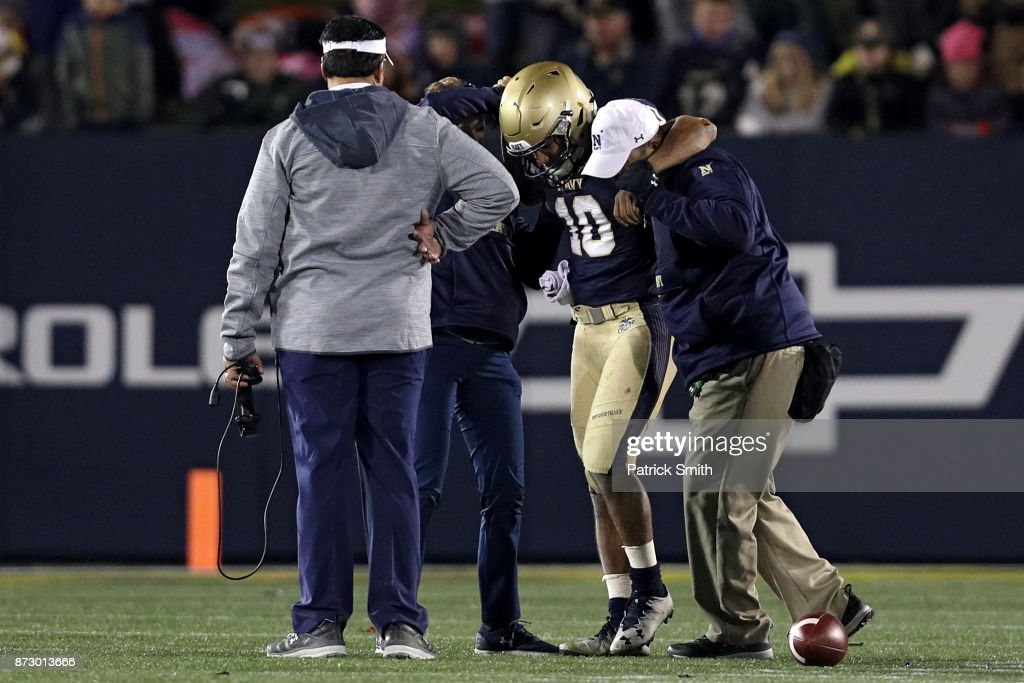 Quarterback Malcolm Perry #10 of the Navy Midshipmen is helped off of the field after being injured against the Southern Methodist Mustangs during the second half at Navy-Marines Memorial Stadium on November 11, 2017 in Annapolis, Maryland.