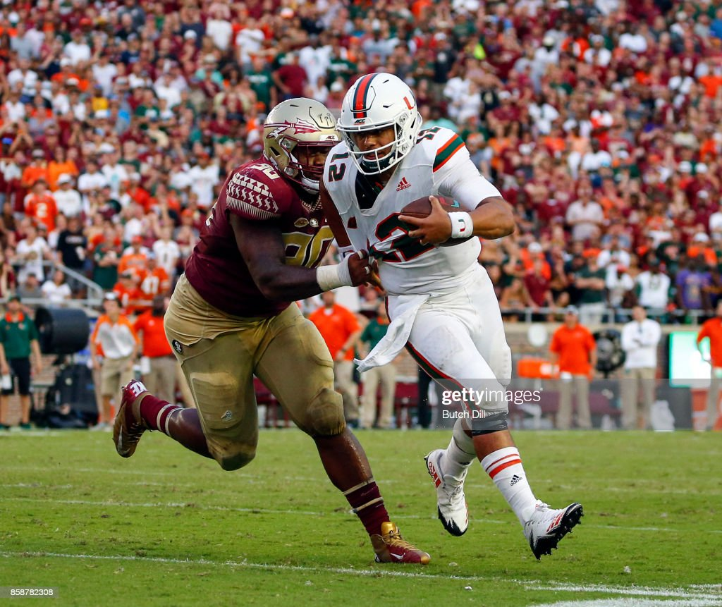 Quarterback Malik Rosier #12 of the Miami Hurricanes tries to break free from the grasp of defensive tackle Demarcus Christmas #90 of the Florida State Seminoles during the second half of an NCAA football game at Doak S. Campbell Stadium on October 7, 2017 in Tallahassee, Florida.
