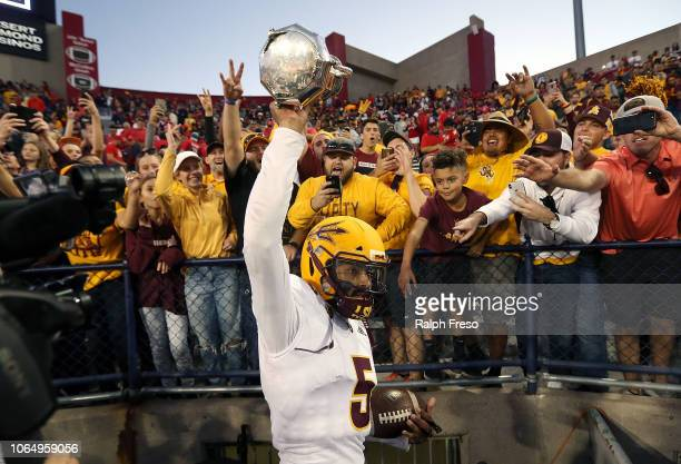 Quarterback Manny Wilkins of the Arizona State Sun Devils holds up the Territorial Cup as he celebrates with fans following a 4140 victory against...