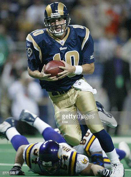 Quarterback Marc Bulger of the St Louis Rams avoids Greg Biekert of the Minnesota Vikings and runs the ball in for a touchdown on November 30 2003 at...