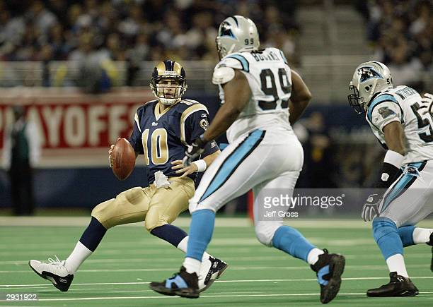 Quarterback Marc Bulger of the St Louis Rams rolls out while under pressure from defensive tackle Brentson Buckner of the Carolina Panthers during...