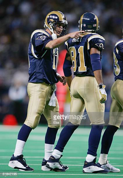 Quarterback Marc Bulger of the St Louis Rams speaks with receiver Torry Holt while facing the New England Patriots on November 7 2004 at the Edward...