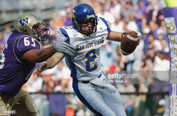 Quarterback Marcus Arroyo of the San Jose State Spartans is pressured in the end zone by Josh Miller of the Washington Huskies during the game on...