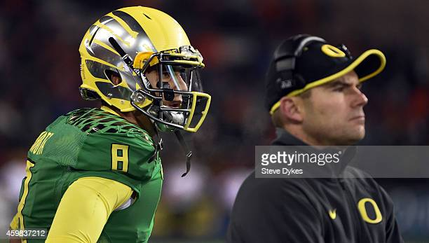 Quarterback Marcus Mariota of the Oregon Ducks and head coach Mark Helfrich of the Oregon Ducks look on from the bench during the third quarter of...