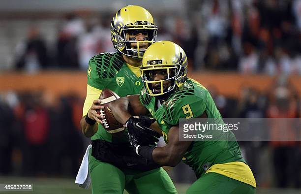 Quarterback Marcus Mariota of the Oregon Ducks fakes a handoff to running back Byron Marshall during the third quarter of the game against the Oregon...