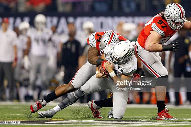 Quarterback Marcus Mariota of the Oregon Ducks gets tackled by linebacker Curtis Grant of the Ohio State Buckeyes in the first quarter during the...