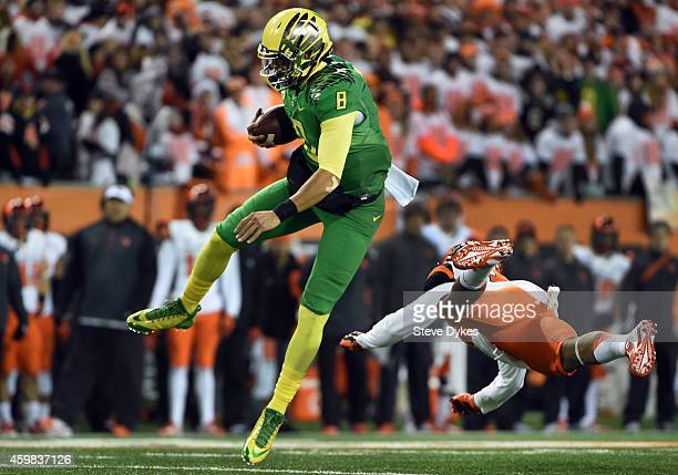 Quarterback Marcus Mariota of the Oregon Ducks hurdles safety Justin Strong of the Oregon State Beavers during the second quarter of the game at...