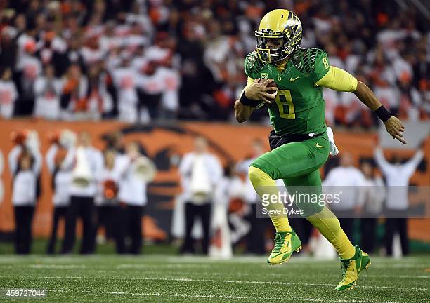 Quarterback Marcus Mariota of the Oregon Ducks runs with the ball during the first quarter of the game against the Oregon State Beavers at Reser...