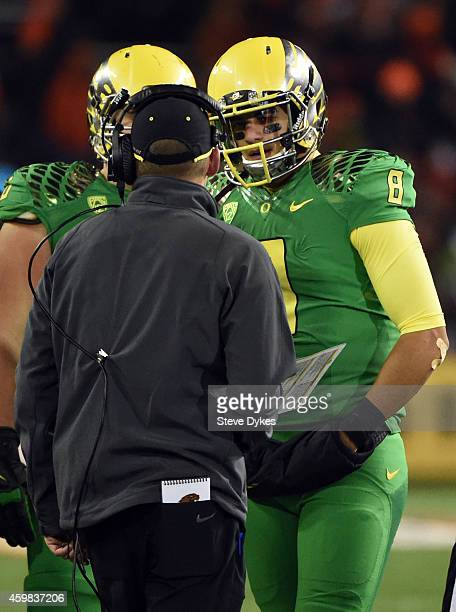 Quarterback Marcus Mariota of the Oregon Ducks speaks with head coach Mark Helfrich of the Oregon Ducks during the third quarter of the game against...