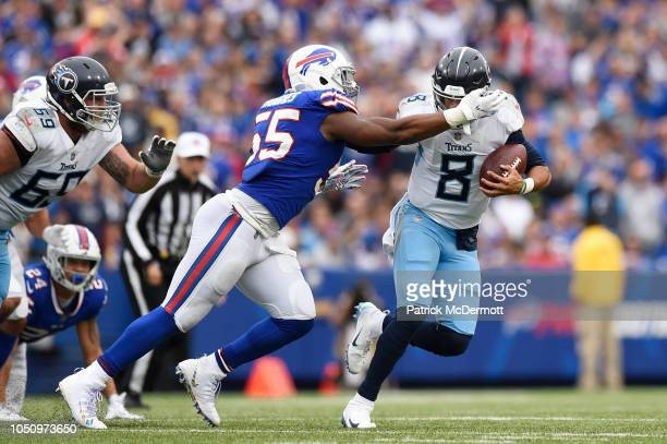 Quarterback Marcus Mariota of the Tennessee Titans fumbles the ball as he is sacked by defensive end Jerry Hughes of the Buffalo Bills in the fourth...