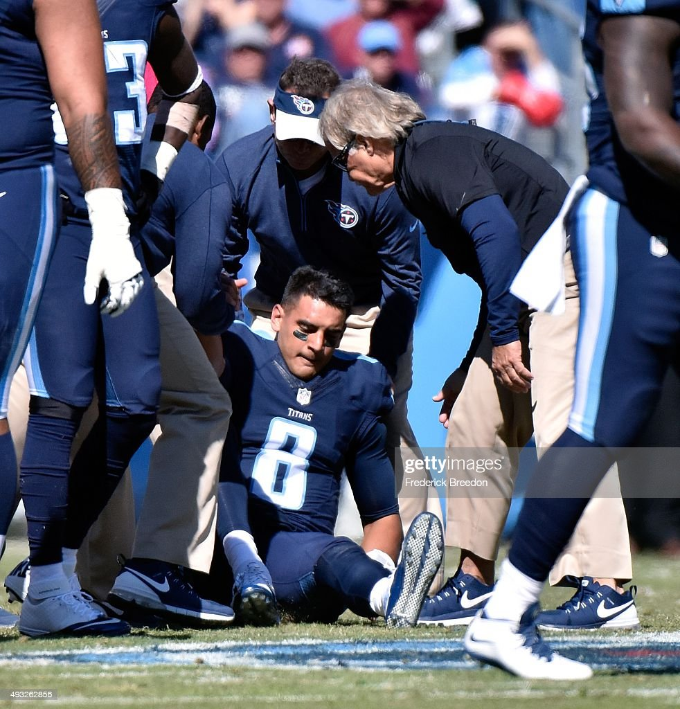 Quarterback Marcus Mariota #8 of the Tennessee Titans is attended to by medical staff after receiving a late hit by the Miami Dolphins during the first half of a game at Nissan Stadium on October 18, 2015 in Nashville, Tennessee.