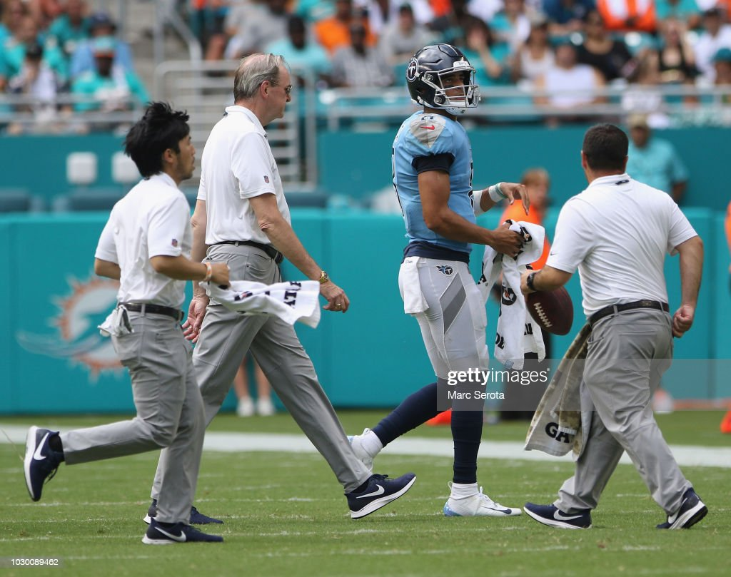 Quarterback Marcus Mariota #8 of the Tennessee Titans is escorted off the field by the trainer after injuring his rist against the Miami Dolphins at Hard Rock Stadium on September 9, 2018 in Miami, Florida.