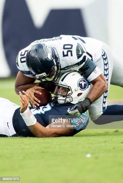 Quarterback Marcus Mariota of the Tennessee Titans is tackled by KJ Wright of the Seattle Seahawks during a NFL game at Nissan Stadium on September...