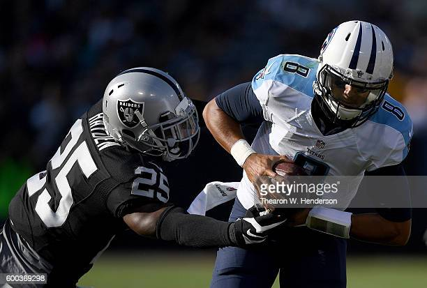 Quarterback Marcus Mariota of the Tennessee Titans runs throw the arm tackle of cornerback D.J. Hayden of the Oakland Raiders in the first half of...
