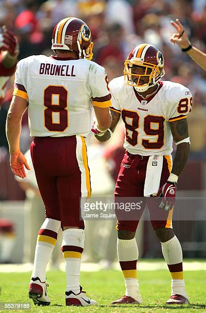 Quarterback Mark Brunell of the Washington Redskins congratulates receiver Santana Moss after the Redskins defeated the Chicago Bears with a final...