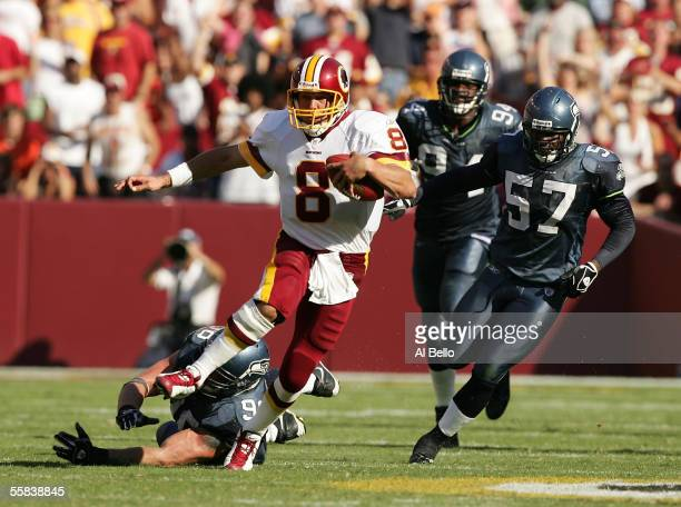 Quarterback Mark Brunell of the Washington Redskins eludes the tackle of Rocky Bernard of the Seattle Seahawks as Kevin Bentley and Bryce Fisher give...