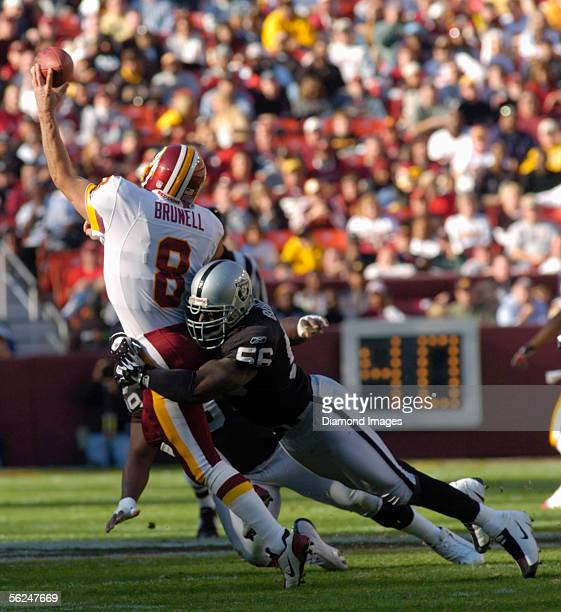 Quarterback Mark Brunell of the Washington Redskins throws a pass just as he is hit by defensive end Derrick Burgess of the Oakland Raiders during a...