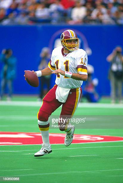 Quarterback Mark Rypien of the Washington Redskins rolls out to pass against the New York Giants during an NFL football game at Giants Stadium...