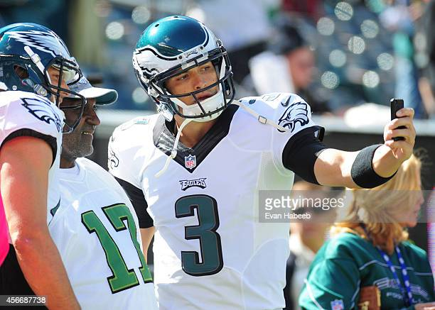 Quarterback Mark Sanchez and wide receiver Riley Cooper of the Philadelphia Eagles take a selfie with a fan prior to the game against the St Louis...