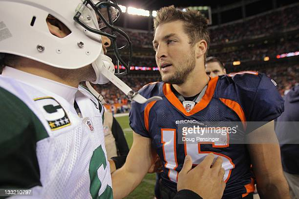 Quarterback Mark Sanchez of the New York Jets and quarterback Tim Tebow of the Denver Broncos meet at midfield after the Broncos defeated the Jets...