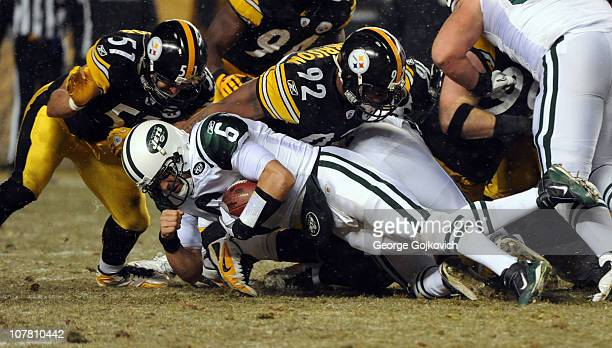 Quarterback Mark Sanchez of the New York Jets is tackled by linebackers James Farrior and James Harrison of the Pittsburgh Steelers during a game at...