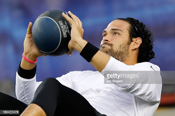 Quarterback Mark Sanchez of the New York Jets stretches before the Jets take on the New England Patriots at Gillette Stadium on September 12 2013 in...