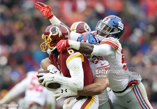 Quarterback Mark Sanchez of the Washington Redskins is sacked by outside linebacker Olivier Vernon and linebacker Lorenzo Carter of the New York...
