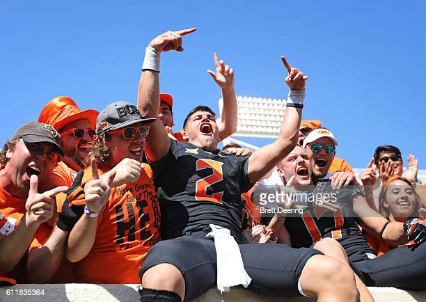 Quarterback Mason Rudolph and wide receiver Austin Hays of the Oklahoma State Cowboys celebrate with fans after the game against the Texas Longhorns...