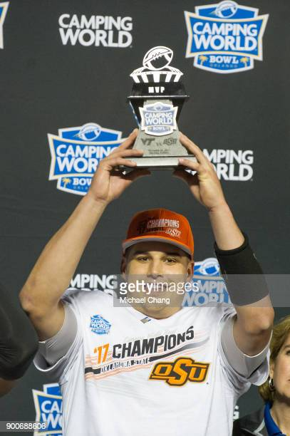Quarterback Mason Rudolph of the Oklahoma State Cowboys holds up the Camping World Bowl MVP trophy after defeating the Virginia Tech Hokies on...