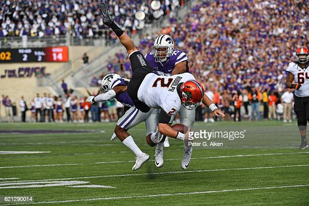 Quarterback Mason Rudolph of the Oklahoma State Cowboys leaps over defensive back Duke Shelley of the Kansas State Wildcats for a first down during...