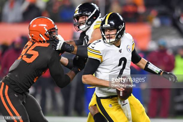 Quarterback Mason Rudolph of the Pittsburgh Steelers moves to avoid pressure from defensive end Myles Garrett of the Cleveland Browns in the second...