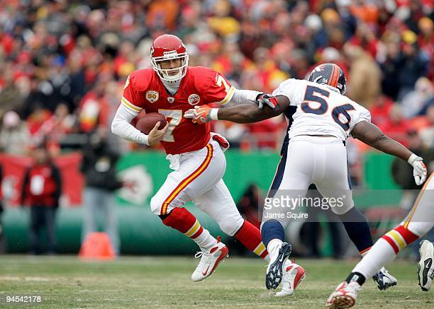 Quarterback Matt Cassel of the Kansas City Chiefs runs with the ball to avoid the tackle of Robert Ayers of the Denver Broncos during their NFL game...