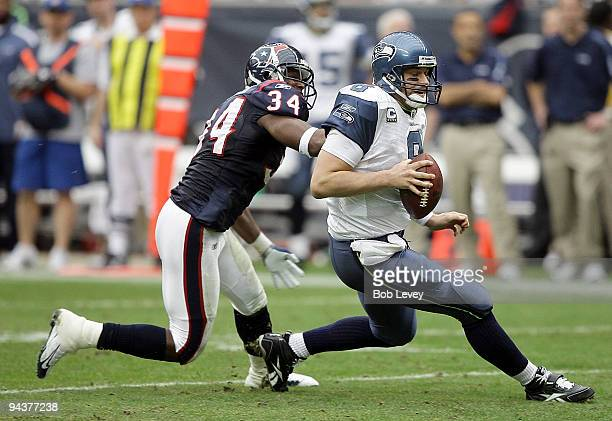 Quarterback Matt Hasselbeck of the Seattle Seahawks avoids being sacked by strong safety Dominique Barber of the Houston Texans at Reliant Stadium on...