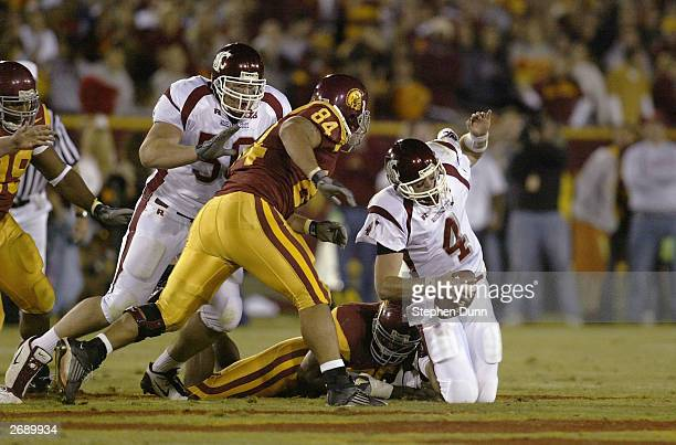 Quarterback Matt Kegel of the Washington State Cougars is brought down by defensive end Omar Nizel of the USC Trojans as defensive tackle Shaun Cody...