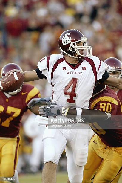 Quarterback Matt Kegel of the Washington State Cougars looks to get rid of the ball as defensive lineman Frostee Rucker of the USC Trojans tries to...