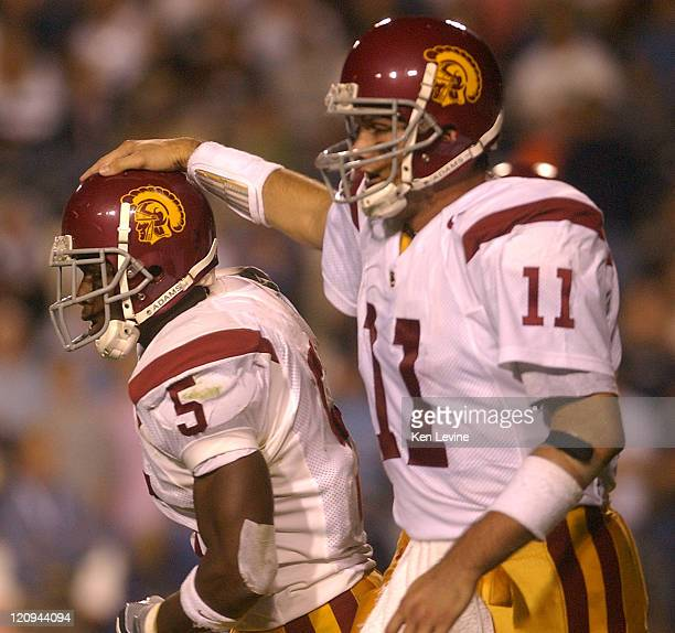 USC quarterback Matt Leinart pats tailback Reggie Bush on the helmet following Bush's 66 yard touchdown run during the second quarter at LaVell...