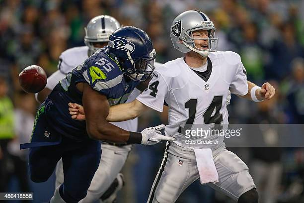 Quarterback Matt McGloin of the Oakland Raiders is sacked in the end zone by defensive end Frank Clark of the Seattle Seahawks at CenturyLink Field...