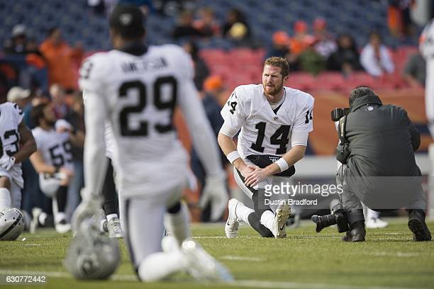 Quarterback Matt McGloin of the Oakland Raiders stretches before the game against the Oakland Raiders at Sports Authority Field at Mile High on...