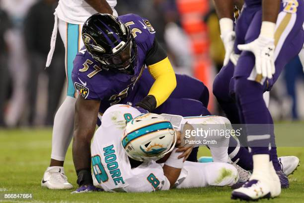 Quarterback Matt Moore of the Miami Dolphins is tackled by inside linebacker CJ Mosley of the Baltimore Ravens in the second quarter at MT Bank...